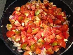 Rödlöken, vitlöken och tomaterna steks i olivolja